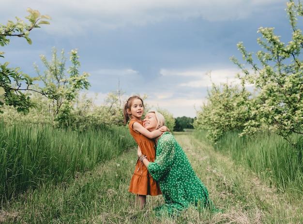 Uma mãe feliz e amorosa abraça sua filha em um pomar de maçãs. o conceito de felicidade familiar