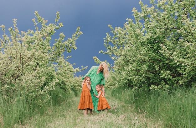 Uma mãe feliz em um vestido verde caminha com suas duas filhas no jardim antes da chuva. felicidade familiar e cuidado materno