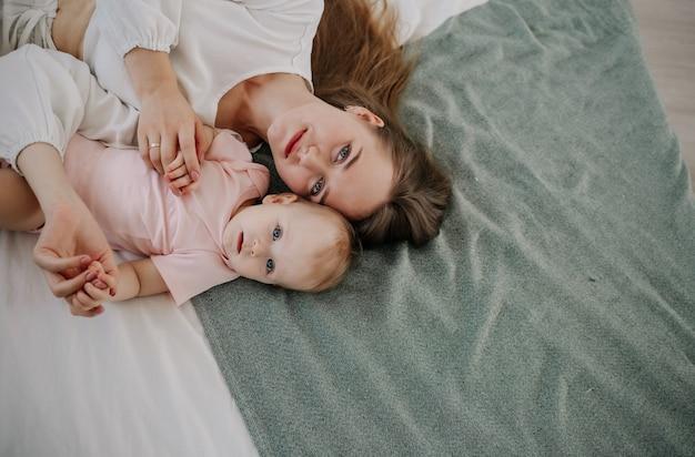 Uma mãe feliz está deitada com sua filha bebê na cama do quarto. vista do topo