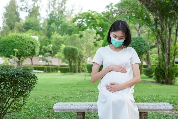 Uma mãe grávida em uma máscara facial de waer roupas casuais brancas senta-se olhando seu bebê no gramado do parque.