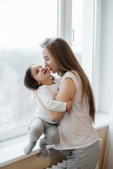 Uma mãe grávida está de pé perto da janela com sua filha.