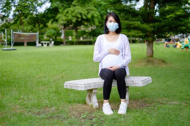 Uma mãe grávida, vestindo roupas casuais branco-púrpura e uma máscara, está sentada no jardim.