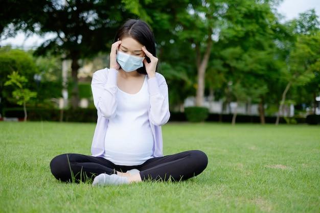 Uma mãe grávida, vestindo roupas casuais roxas e brancas, está sentada no jardim com uma dor de cabeça doentia.
