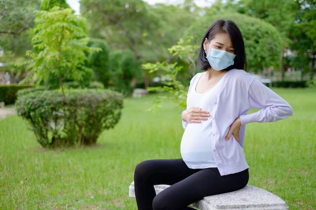 Uma mãe grávida, vestindo roupas casuais roxas e brancas, está sentada no jardim com uma dor de estômago doentia.