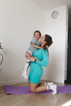 Uma mãe jovem e atlética em um agasalho abraça a filha após um treino conjunto de fitness