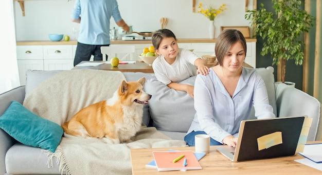 Uma mãe ocupada tenta trabalhar remotamente com o filho e o marido em casa.