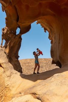 Uma mãe se divertindo com seu bebê no mirador de la peñitas no canyon peñitas, fuerteventura, ilhas canárias. espanha