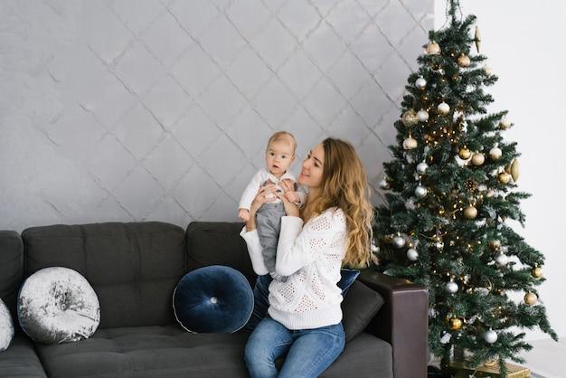 Uma mãe segura seu filho nos braços e sorri para ele enquanto está sentado perto de uma árvore de natal na sala de estar em sua casa