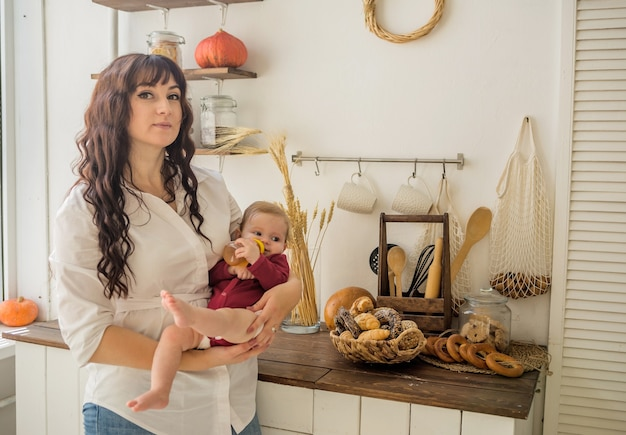 Uma mãe segura uma menina nos braços com uma garrafa de suco na cozinha e olha para a câmera