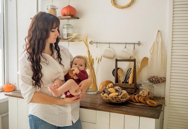 Uma mãe segura uma menina nos braços com uma garrafa de suco na cozinha