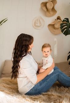 Uma mãe segura uma menina nos braços e olha para ela em um quarto de casa