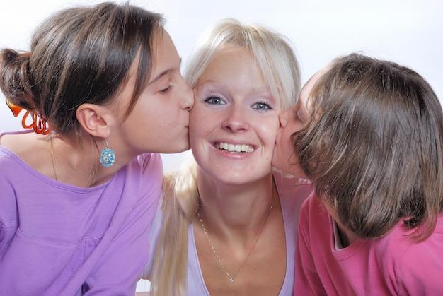 Uma mãe sorri quando recebe um beijo na bochecha dela, você