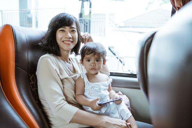 Uma mãe sorridente e feliz e uma garotinha segurando um celular enquanto estão sentadas perto da janela no ônibus