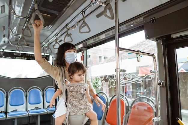 Uma mãe usa uma máscara e carrega seu filho enquanto está no ônibus no caminho
