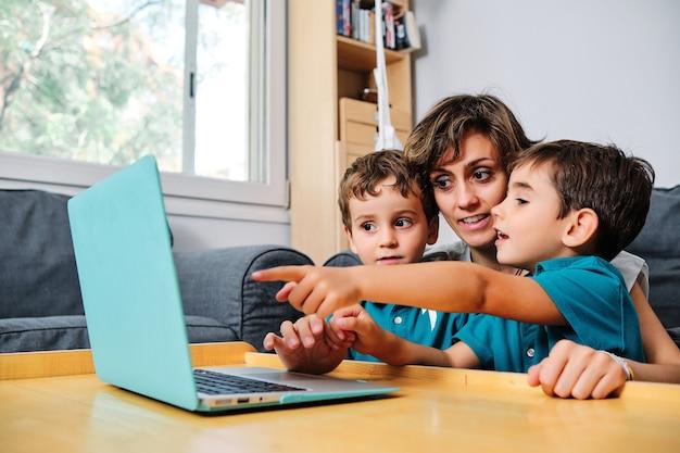Uma mãe usando um computador para ensinar seus filhos em casa