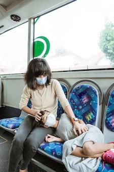Uma mãe usando uma máscara e sua filha estão dormindo em um banco enquanto viajam de ônibus