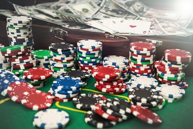 Uma mala cheia de dinheiro com fichas e cartas na mesa de pôquer
