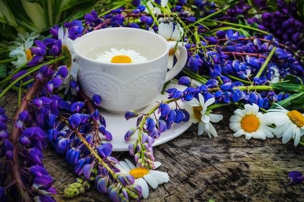 Uma manhã de verão, uma xícara de café branco e um buquê de flores silvestres