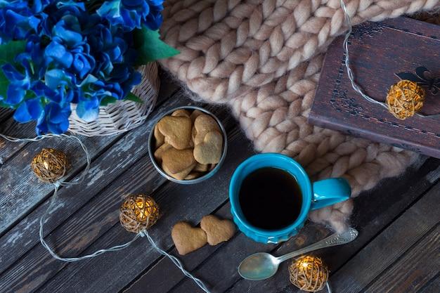 Uma manta, um livro, uma caneca de chá azul, uma guirlanda e biscoitos