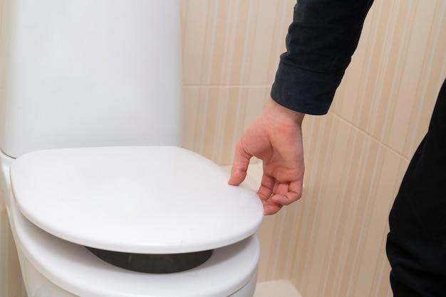 Uma mão abre a tampa do vaso sanitário, sanitários domésticos domésticos