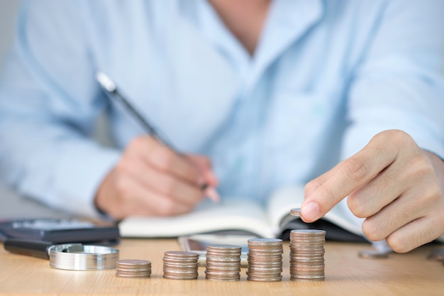 Uma mão colocando moedas empilhamento e uma mão escrevendo registro para negócios de crescimento e salvando o conceito de investimento.