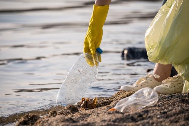 Uma mão com luva de borracha levanta uma garrafa de plástico da água como voluntária para a limpeza de sábado