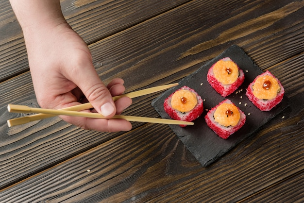 Uma mão com os pauzinhos tira um pãozinho de um prato. comida tradicional japonesa.