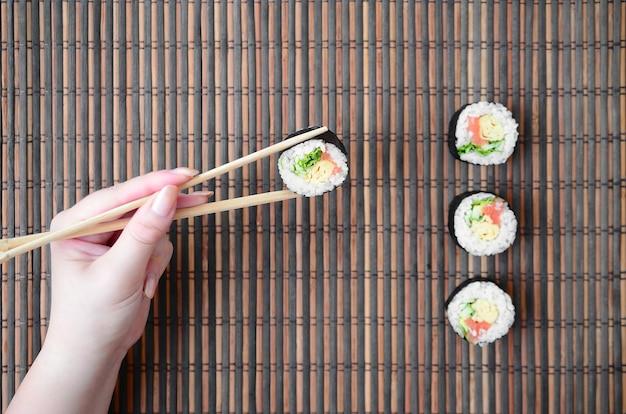 Uma mão com pauzinhos segura um rolo de sushi na parede da esteira de palha de bambu. comida tradicional asiática.