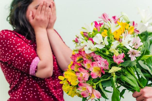 Uma mão com um bouquet exuberante de flores estende as flores para uma mulher