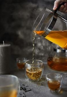 Uma mão com um bule derrama chá fervente em uma xícara durante o café da manhã. taça com vapor