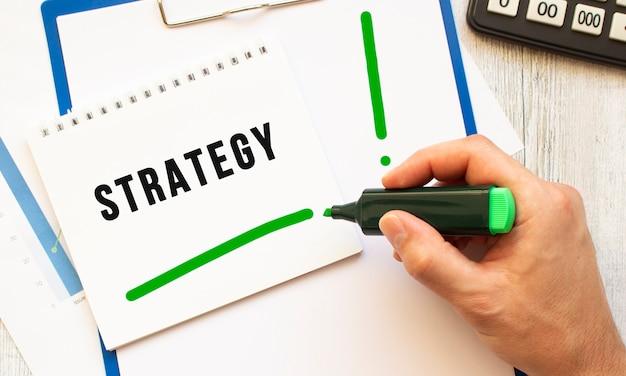 Uma mão com um marcador escreve o texto estratégia em um caderno na área de trabalho. vista de cima. conceito de negócios.