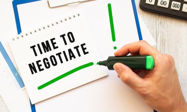 Uma mão com um marcador escreve o texto hora de negociar em um caderno na área de trabalho. vista de cima. conceito de negócios.