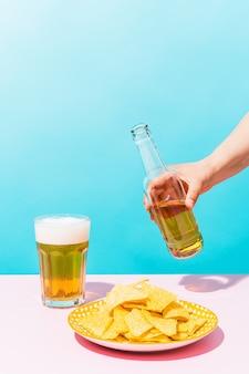 Uma mão com uma cerveja ao lado de um prato de nachos em um fundo azul comida méxico e verão