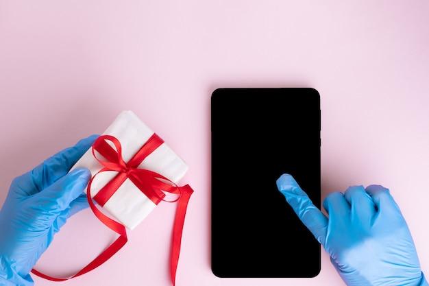 Uma mão com uma luva protetora azul pressiona uma tela preta em branco de um tablet ou telefone, a outra mão com uma luva protetora segura um presente em um fundo rosa. conceito de saudações de feriado seguro