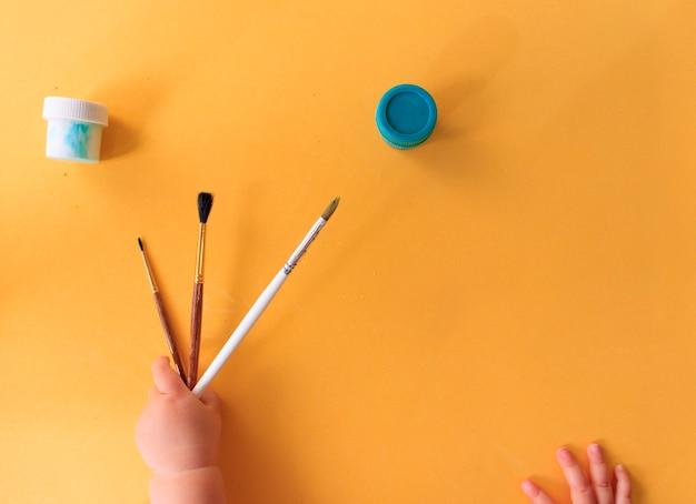 Uma mão de bebê desenhando linhas e formas com giz de cera colorido.