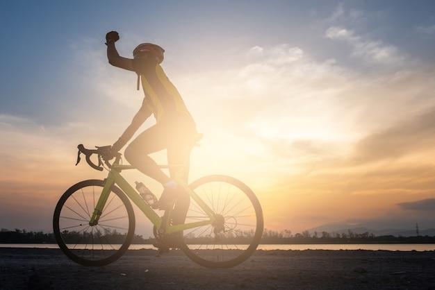 Uma mão de ciclista e andar de bicicleta de estrada na estrada de manhã