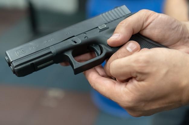Uma mão de homem praticando tiro usando um modelo de arma glock no campo de tiro.