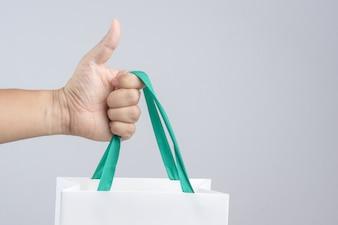 Uma mão de homem segurando o saco de compras com o polegar para cima gesto