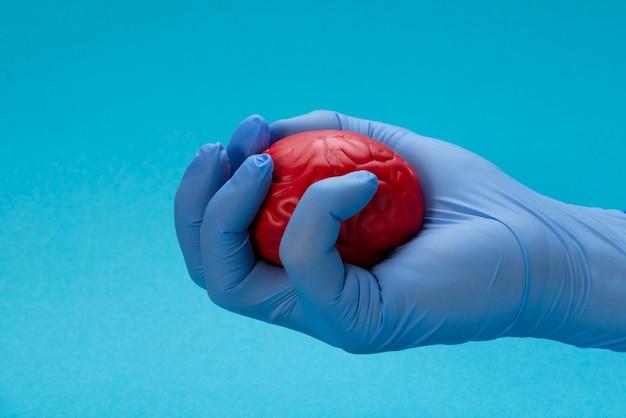 Uma mão de luva de látex aperta um cérebro vermelho.
