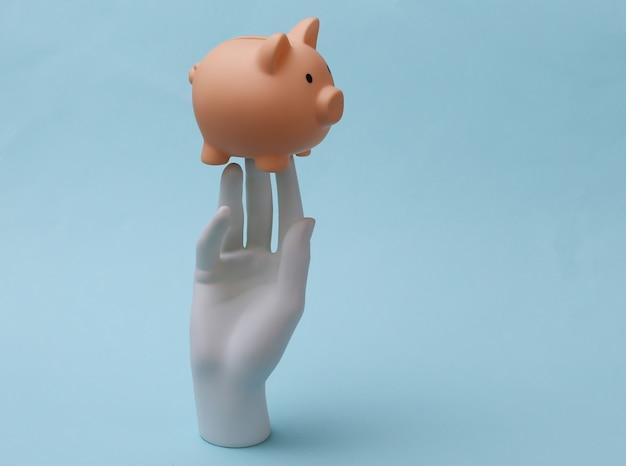 Uma mão de manequim branco segura o cofrinho sobre fundo azul. finanças, conceito de economia
