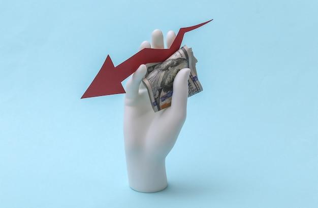 Uma mão de manequim branco segura uma seta caindo apontando para baixo com notas de dólar em um fundo azul. conceito econômico, a taxa do dólar salta