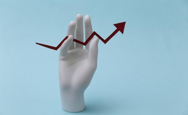 Uma mão de manequim branco segura uma seta de crescimento apontando para cima em um fundo azul. negócios, conceito de economia