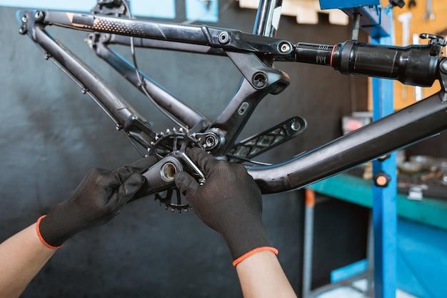 Uma mão de mecânico usando luvas instalando o braço da manivela direito no suporte inferior