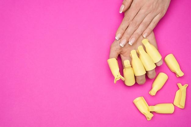 Uma mão de mulher com um conjunto de unhas artísticas de plástico para imersão na tampa clipe de removedor de polonês de gel uv ferramenta de envoltório de removedor de esmalte de gel uv para cuidar das unhas em casa de goma-laca em fundo rosa