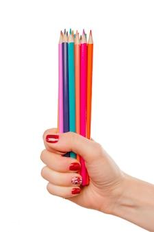 Uma mão de mulher segura lápis de cor de variedade (colorido) como um arco-íris na mesa branca