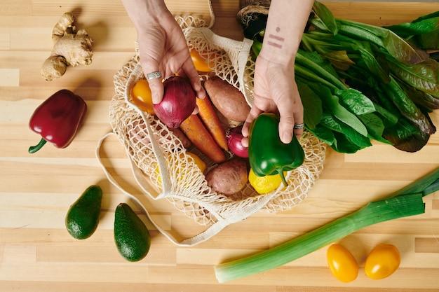 Uma mão de mulher tirando legumes frescos da sacola de compras na mesa da cozinha de madeira