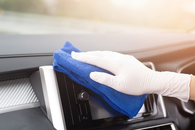Uma mão de trabalhador usa luva para limpar o volante do console do carro com pano de microfibra