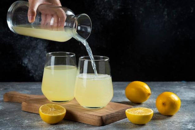 Uma mão derramando suco de limão em um copo de vidro.