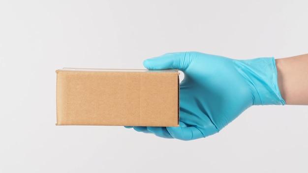 Uma mão direita usando luva médica azul e segurando uma caixa marrom no fundo branco.