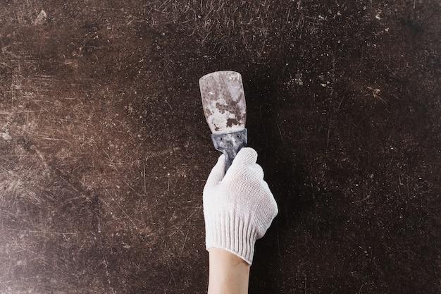 Uma mão em luvas de trabalho com uma espátula em um fundo de mármore escuro. faça reformas